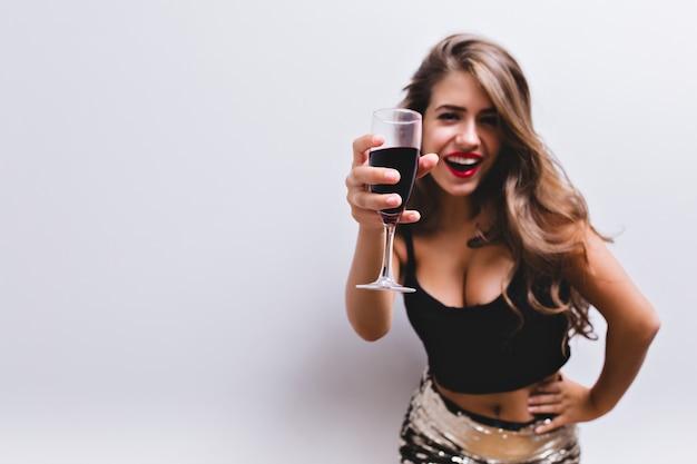 微笑し、トーストでワインのグラスを上げる美しい少女。彼女はスパンコール付きスカート、黒のトップを着ています。裸の腹と深い谷間を備えたセクシーでスタイリッシュな外観。赤ワインのグラスに焦点を当てます。分離されました。 無料写真
