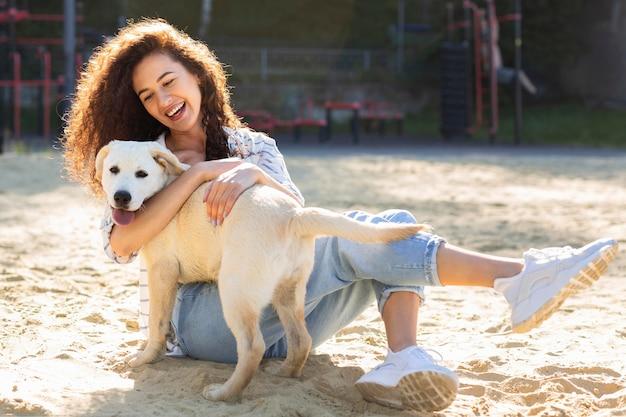 彼女の犬を抱きしめながら笑っている美しい女の子 Premium写真