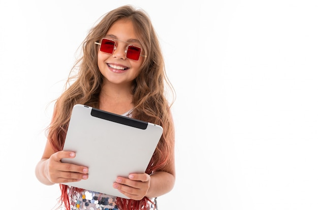 Beautiful girl in square red sunglasses holding grey tablet Premium Photo