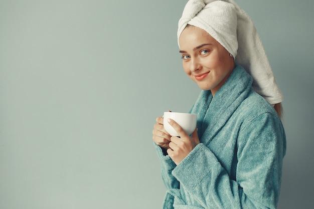 Beautiful girl standing  in a blue bathrobe Free Photo