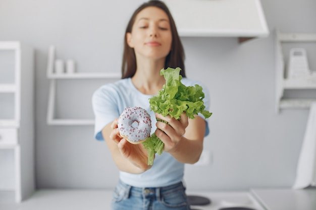 Beautiful girl standing in a kitchen with donut and leaf Free Photo
