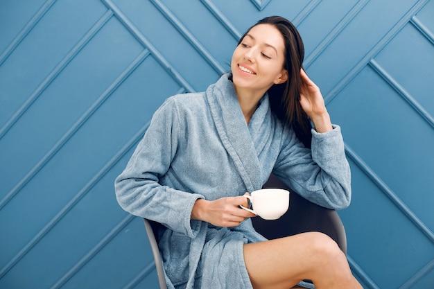 Beautiful girl standing in a studio in a blue bathrobe Free Photo