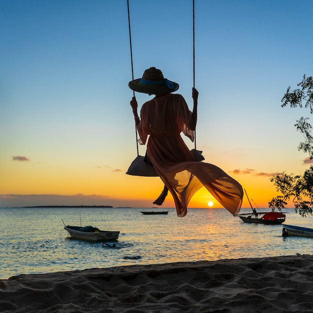 Beautiful girl in a straw hat and pareo swinging on a swing on the beach during sunset of zanzibar island, tanzania, africa. travel and vacation concept Premium Photo