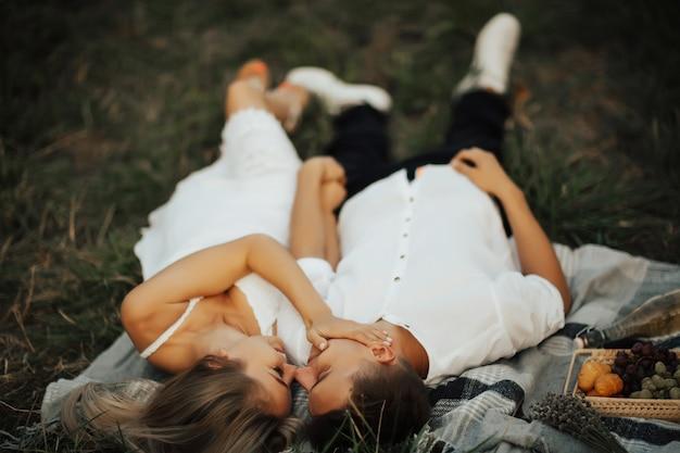 Красивая девушка гладит лицо парня на романтическом пикнике в парке, лежа на зеленой траве. Premium Фотографии