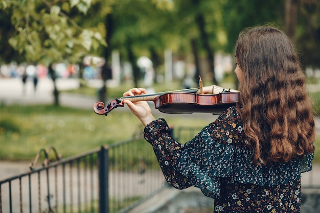 Beautiful girl in a summer park with a violin Free Photo