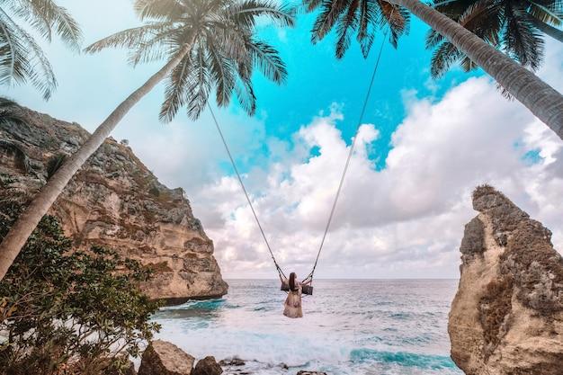 Beautiful girl on swing coconut palms on beach at daimond beach, nusa penida island bali ,indonesia Premium Photo