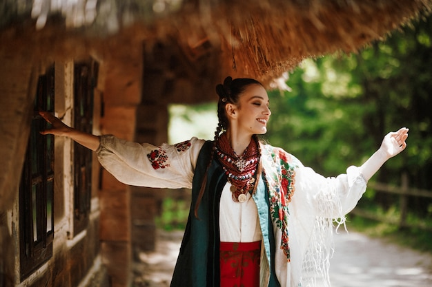 Beautiful girl in a traditional ukrainian dress dances and smiles Free Photo
