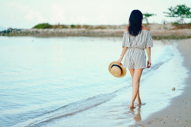 Beautiful girl walking along the beach in thailand Premium Photo