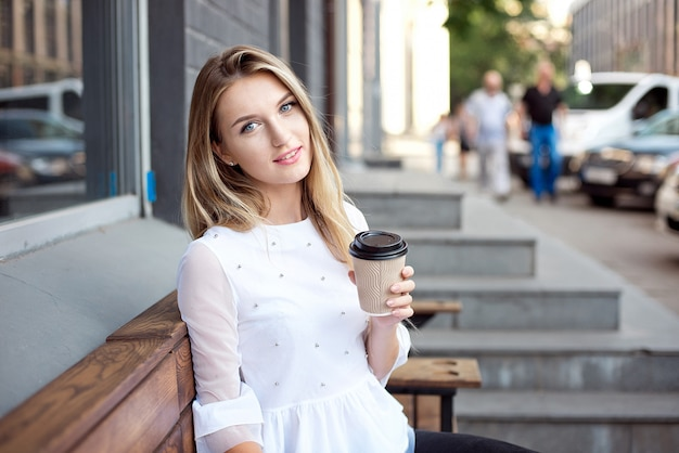 Beautiful girl walking in the city and drinking takes away coffee by an outdoor cafe. city morning scene. Premium Photo