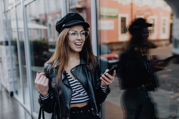 Beautiful girl walks on the street in black leather jacket after rain Free Photo