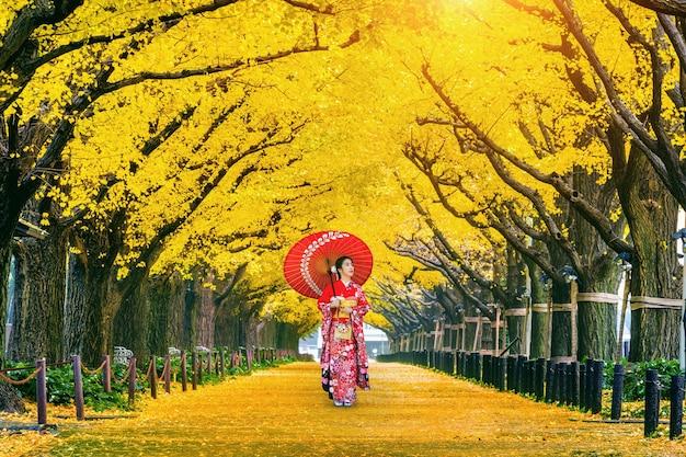 秋の黄色い銀杏の木の列で日本の伝統的な着物を着ている美しい少女。東京の秋の公園。 無料写真