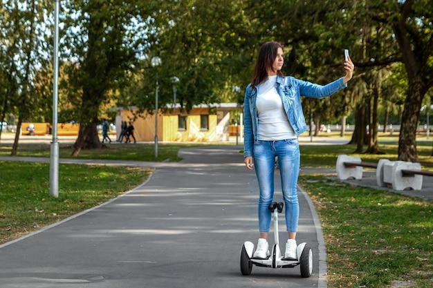 Beautiful girl on a white hoverboard in the park Premium Photo