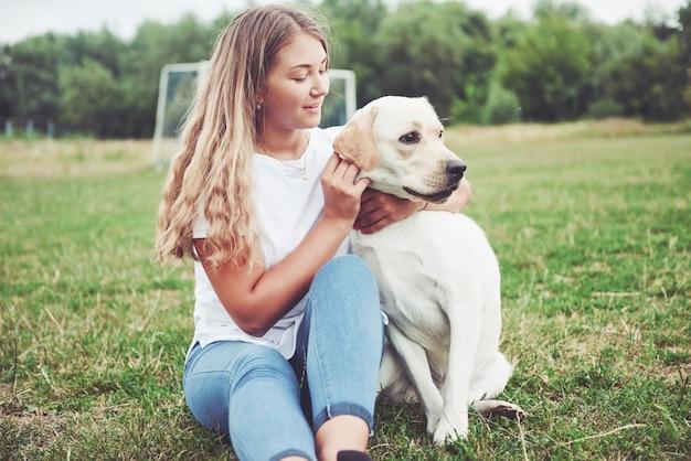 緑の芝生の公園で美しい犬と美しい少女。 無料写真