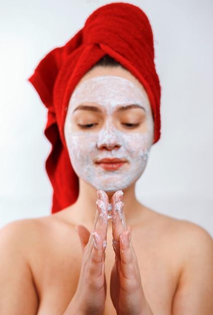 彼女の頭に赤いタオルを持つ美しい少女は顔にスクラブを適用します Premium写真