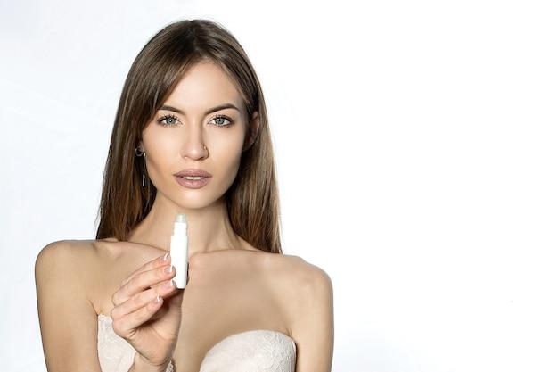 Красивая девушка с открытыми плечами рекламирует косметику на белом. Premium Фотографии