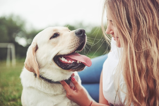 Beautiful girl with a beautiful dog in a park on green grass. Premium Photo