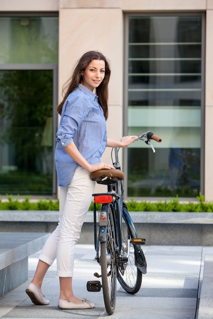 Beautiful girl with a bicycle on the road Free Photo