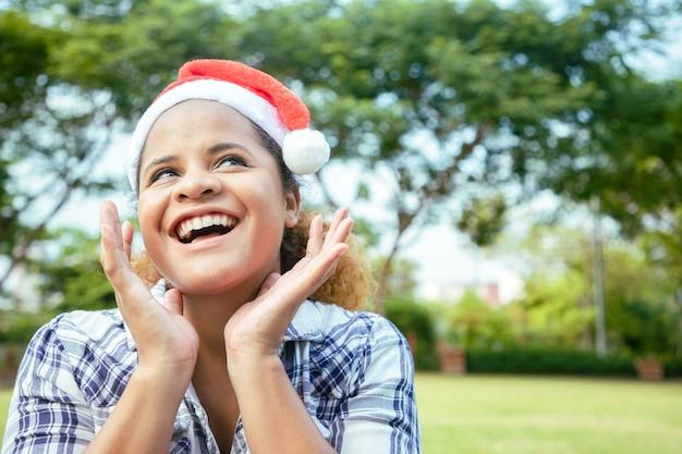 家の前の庭でサンタクロースの帽子をかぶった明るい笑顔の美しい少女。 Premium写真