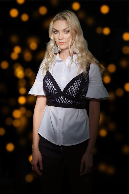 Красивая девушка с чистой и здоровой кожей позирует в темной комнате с огнями на фоне Premium Фотографии
