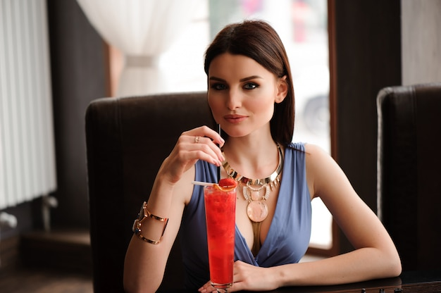 Beautiful girl with a cocktail at the cafe. Premium Photo