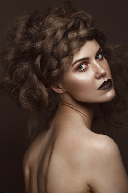 Beautiful girl with creative hairstyle art, perfect skin and dark makeup. the beauty of the face. Premium Photo