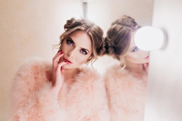 탈의실에서 사진 촬영을 기다리는 동안 그녀의 얼굴을 만지고 귀여운 헤어 스타일을 가진 아름 다운 소녀. 메이크업 거울 옆에 포즈 관심을 가진 찾고 핑크 재킷에 화려한 곱슬 젊은 여자 무료 사진