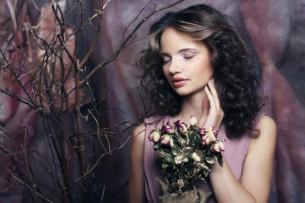 Beautiful girl with dry roses Premium Photo