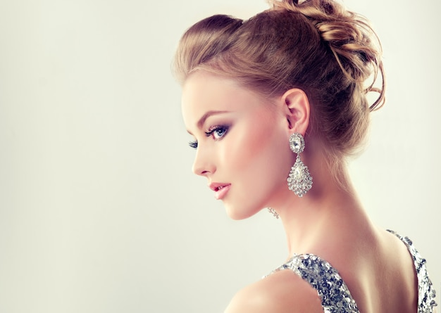 Beautiful girl with elegant hairstyle and big earrings jewelry Premium Photo