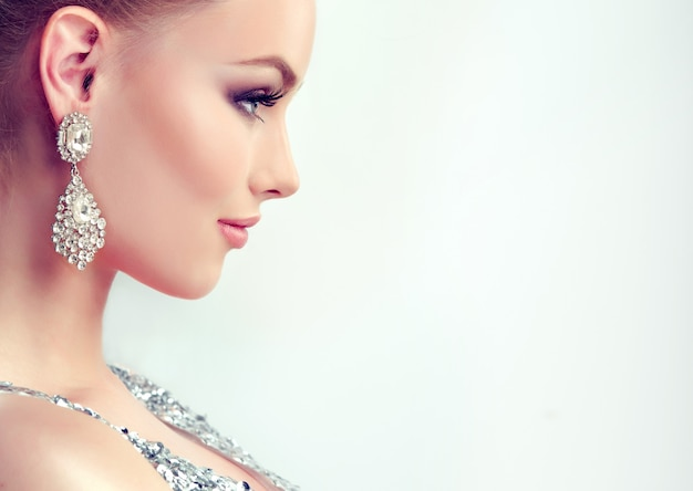 Beautiful girl with evening makeup and  large earrings jewelry Premium Photo