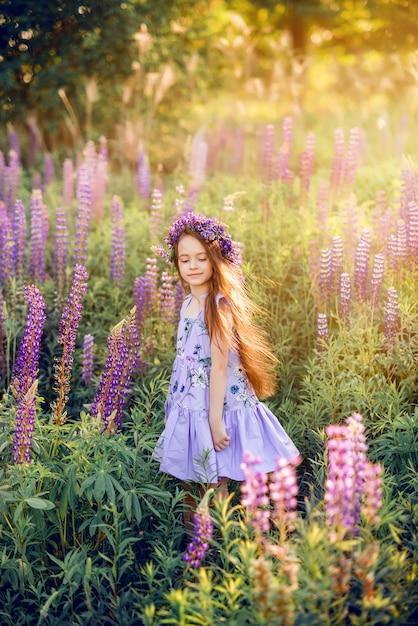 Красивая девушка с цветами в ее волосы среди цветов. солнечное летнее фото с ребенком в фиолетовых цветах Premium Фотографии