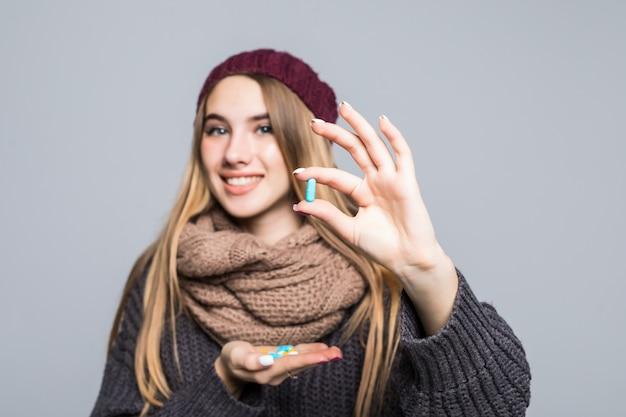 Красивая девушка с гриппом или простудой должна принять много таблеток, чтобы стать здоровой на сером Бесплатные Фотографии