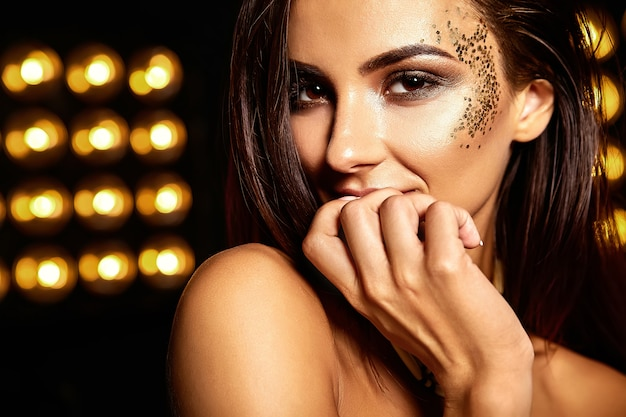 Beautiful girl with golden glitter on the face Free Photo
