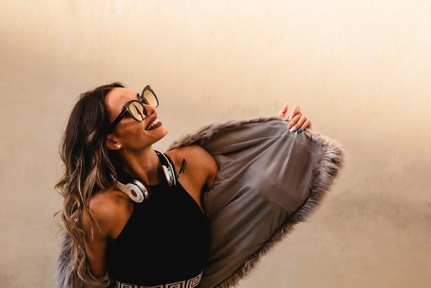 ヘッドフォンで美しい少女は音楽を聴き、屋外で踊ります。白い壁の背景 Premium写真