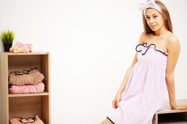 シャワーの後タオルドレスで健康な皮膚を持つ美しい少女 Premium写真