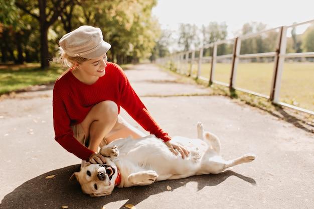 Bella ragazza con il suo cane che giocano insieme nel parco. elegante bionda e il suo animale domestico rilassante sotto il sole in autunno. Foto Gratuite