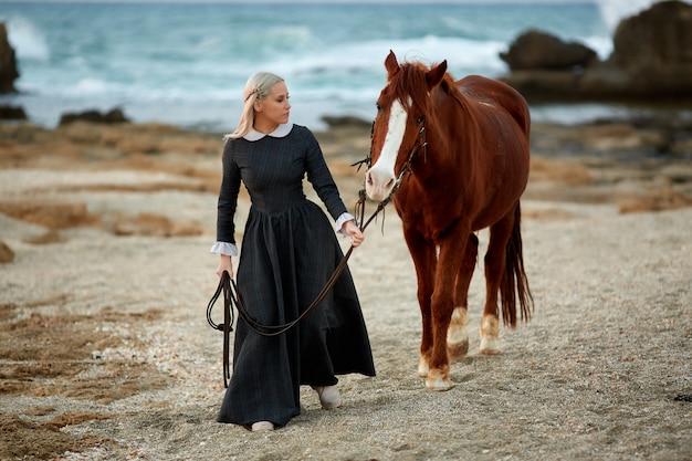Beautiful girl with horse on seacoast Premium Photo