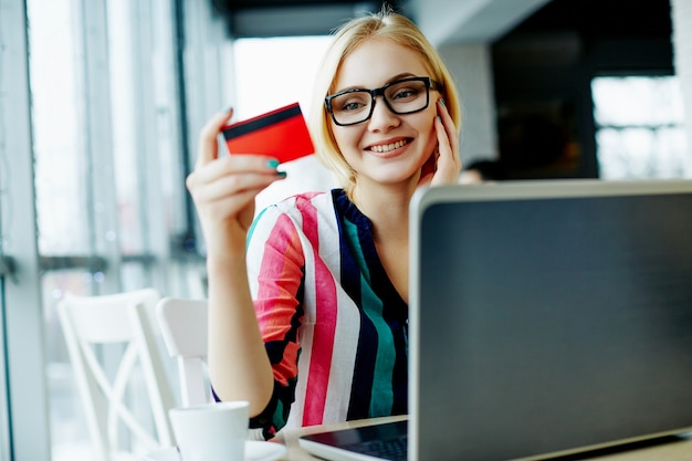 Beautiful girl with light hair wearing colorful shirt and glasses sitting in cafe with laptop and credit card, freelance concept, online shopping, smiling. Premium Photo