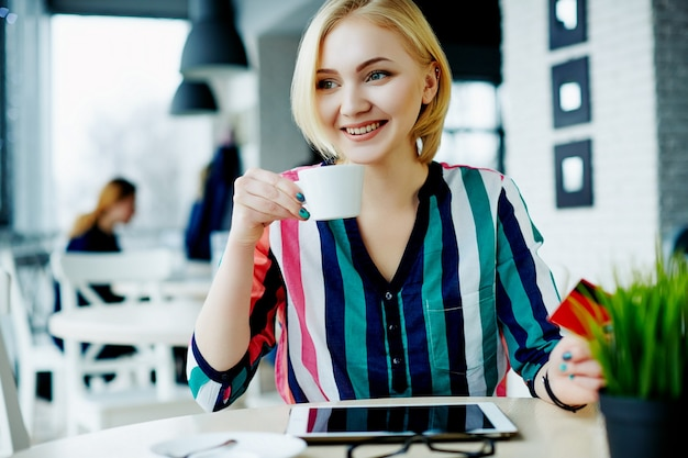 Beautiful girl with light hair wearing colorful shirt sitting in cafe with tablet, mobile phone and cup of coffee, freelance concept, online shopping. Premium Photo