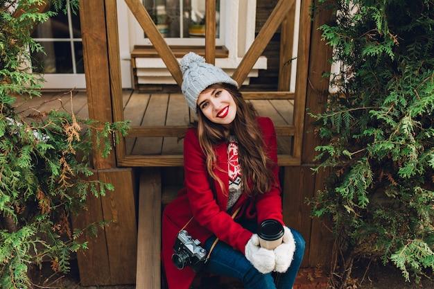 屋外の緑の枝の間の木製の階段の上に座って赤いコートに長い髪の美しい少女。彼女は白い手袋と笑顔でコーヒーを保持しています。上からの眺め。 無料写真