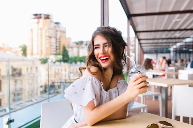 긴 머리를 가진 아름 다운 소녀는 카페의 테라스 테이블에 앉아있다. 그녀는 벌거 벗은 어깨와 빨간 립스틱으로 하얀 드레스를 입는다. 그녀는 갈 컵을 들고 옆으로 미소를 지었다. 무료 사진