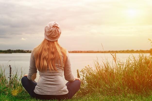 長い髪の美しい少女は海岸に座っています。後ろからの眺め。日没。平和と静けさ。 Premium写真