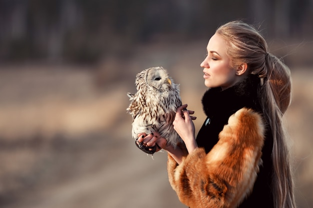 Beautiful girl with long hair nature, holding owl Premium Photo