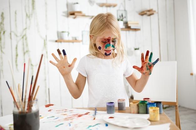 白い紙に彼女の手で描く白いtシャツを着て塗られた顔で美しい少女 無料写真