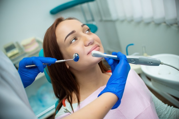 Beautiful girl with red hair is sitting in the dental chair Premium Photo