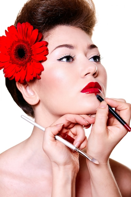 Beautiful girl with red lips and nails doing her make up Free Photo