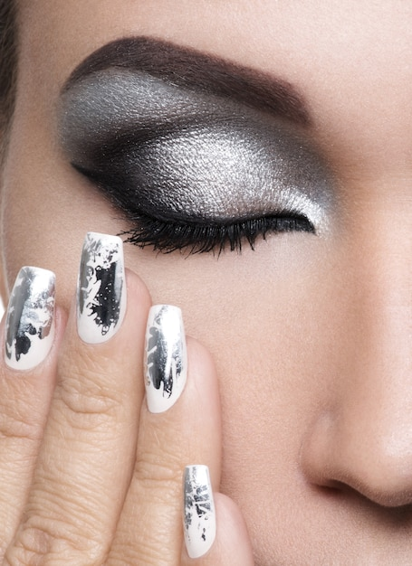Bella ragazza con il trucco d'argento degli occhi e dei chiodi di metallo. Foto Gratuite