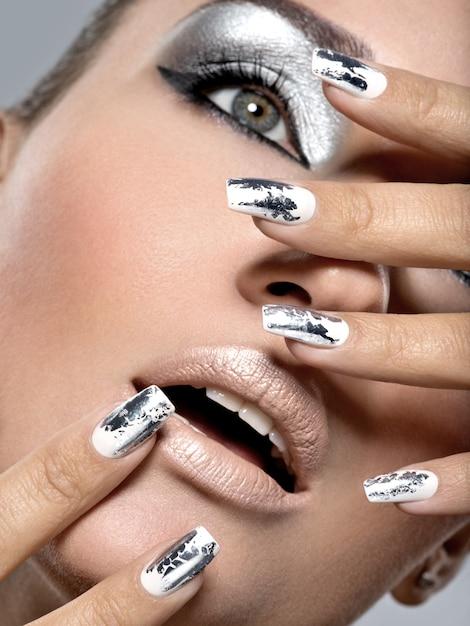 Bella ragazza con il trucco d'argento e chiodi di metallo. ritratto di donna di moda. Foto Gratuite