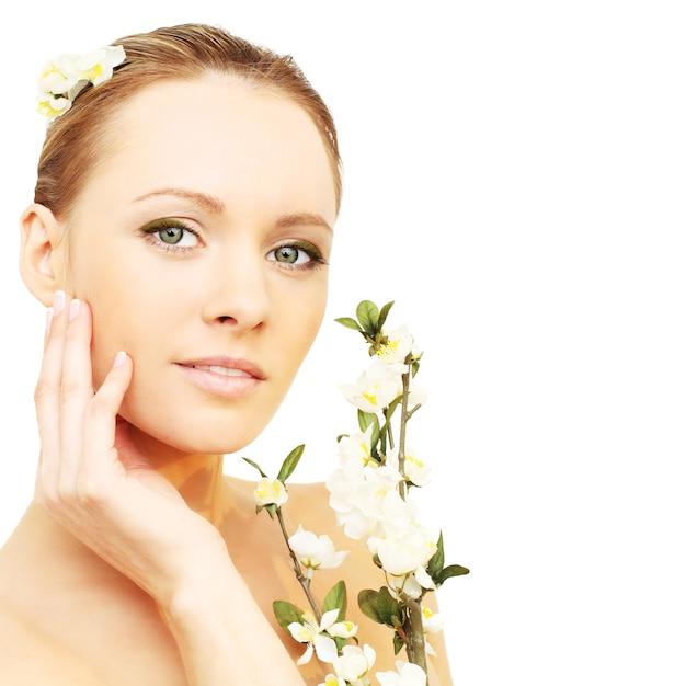 白で隔離春の花を持つ美しい少女 Premium写真