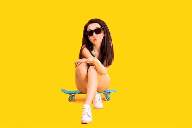 Красивая девушка в солнцезащитных очках сидит на скейтборде Premium Фотографии