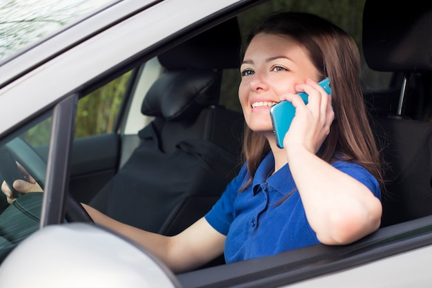 Красивая девушка, молодая женщина за рулем автомобиля, улыбаясь и говорить на свой мобильный телефон. использование смартфона за рулем автомобиля, за рулем. опасная ситуация, не обращая внимания на дорогу Premium Фотографии